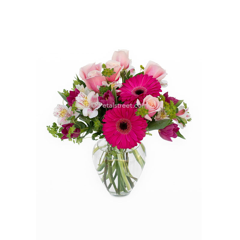 Mixed vase arrangement in a variety of pinks. Gerbera Daisies, Roses, Alstromeria, and accents.