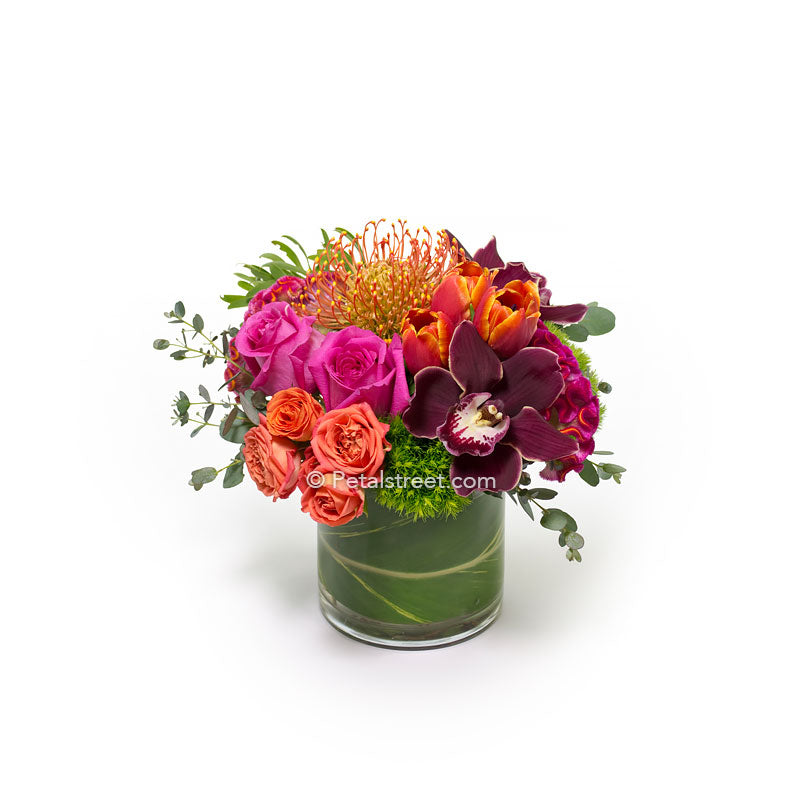Pink Roses, burgundy Orchids, orange Pincushion Protea make up this vibrant flower arrangement by Petal Street Flower Co.