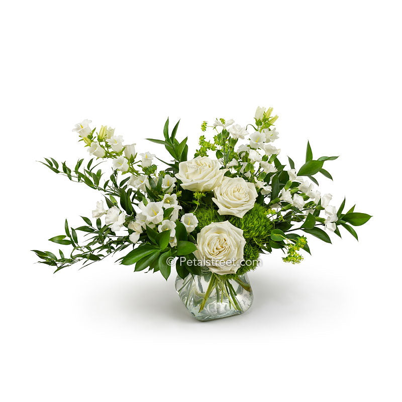 Vase of all white flowers featuring Roses mixed with accent flowers and foliage arranged garden style.