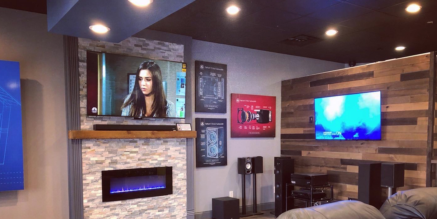 About Us – AC Audio Video Showroom with a flatscreen tv hanging on a stone wall with sound bar over a fireplace, beige leather couch and another flat panel tv on wall with free standing speakers and audio components on side wall.