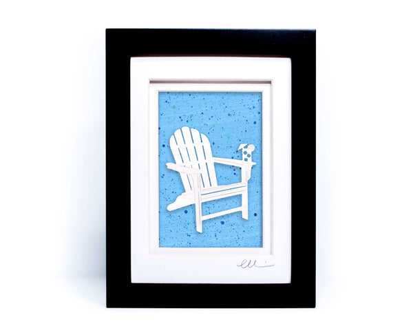 White beach adirondack chair with drink on chair arm papercut on hand painted light blue splattered background.