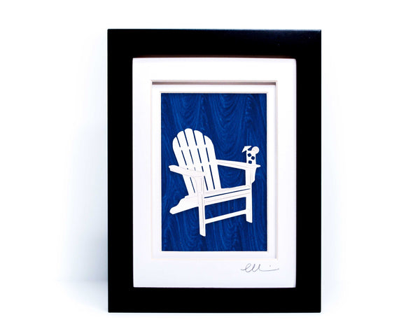 White beach adirondack chair with drink on chair arm papercut on hand painted blue wave background.