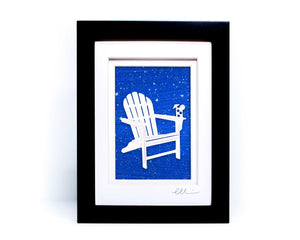 White beach adirondack chair with drink on chair arm papercut on hand painted bright blue splattered background.