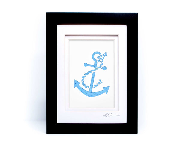 White nautical anchor twisted with rope papercut on hand painted light blue splattered background.
