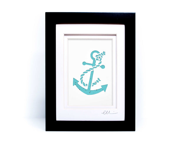 White nautical anchor twisted with rope papercut on hand painted teal background.