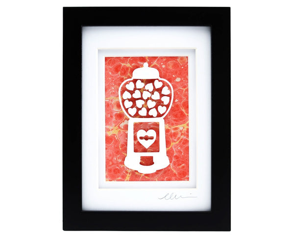 Framed heart filled gumball machine paper cut with red hand marbled paper background.