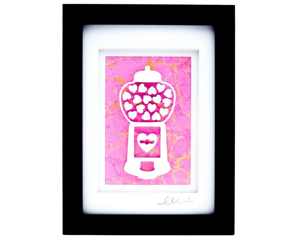 Framed heart filled gumball machine paper cut with pink hand marbled paper background.
