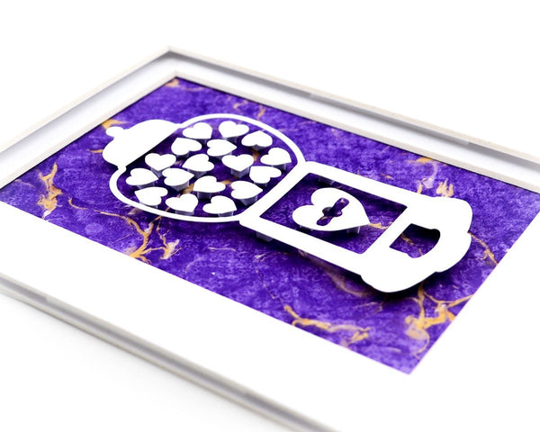 Unframed heart filled gumball machine paper cut with purple hand marbled paper background.