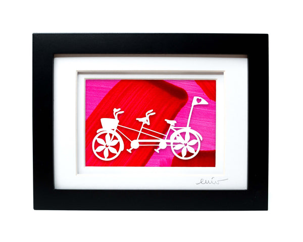 White tandem couples bike with heart flag papercut on hand painted pink and red background.