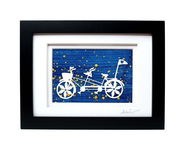 White tandem couples bike with heart flag papercut on hand painted dark blue splattered background.