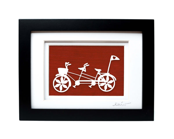 White tandem couples bike with heart flag papercut on hand painted red background.