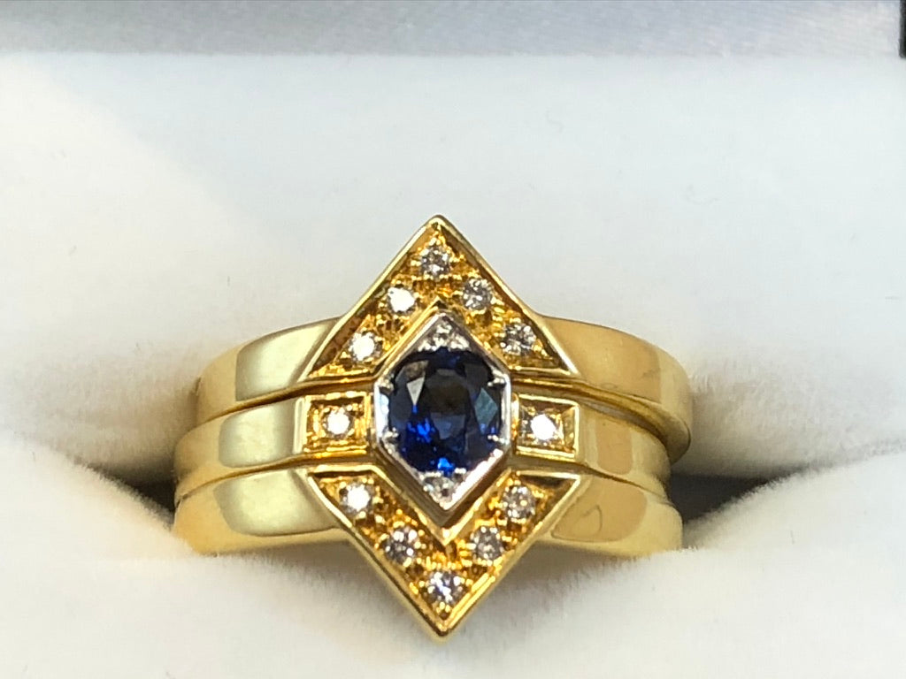 A close up of three 18ct yellow gold bands with a central sapphire and diamond surrounds
