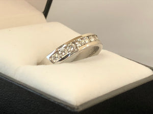 A side on extra close up of a 9-stone channel set diamond ring in 18ct white gold