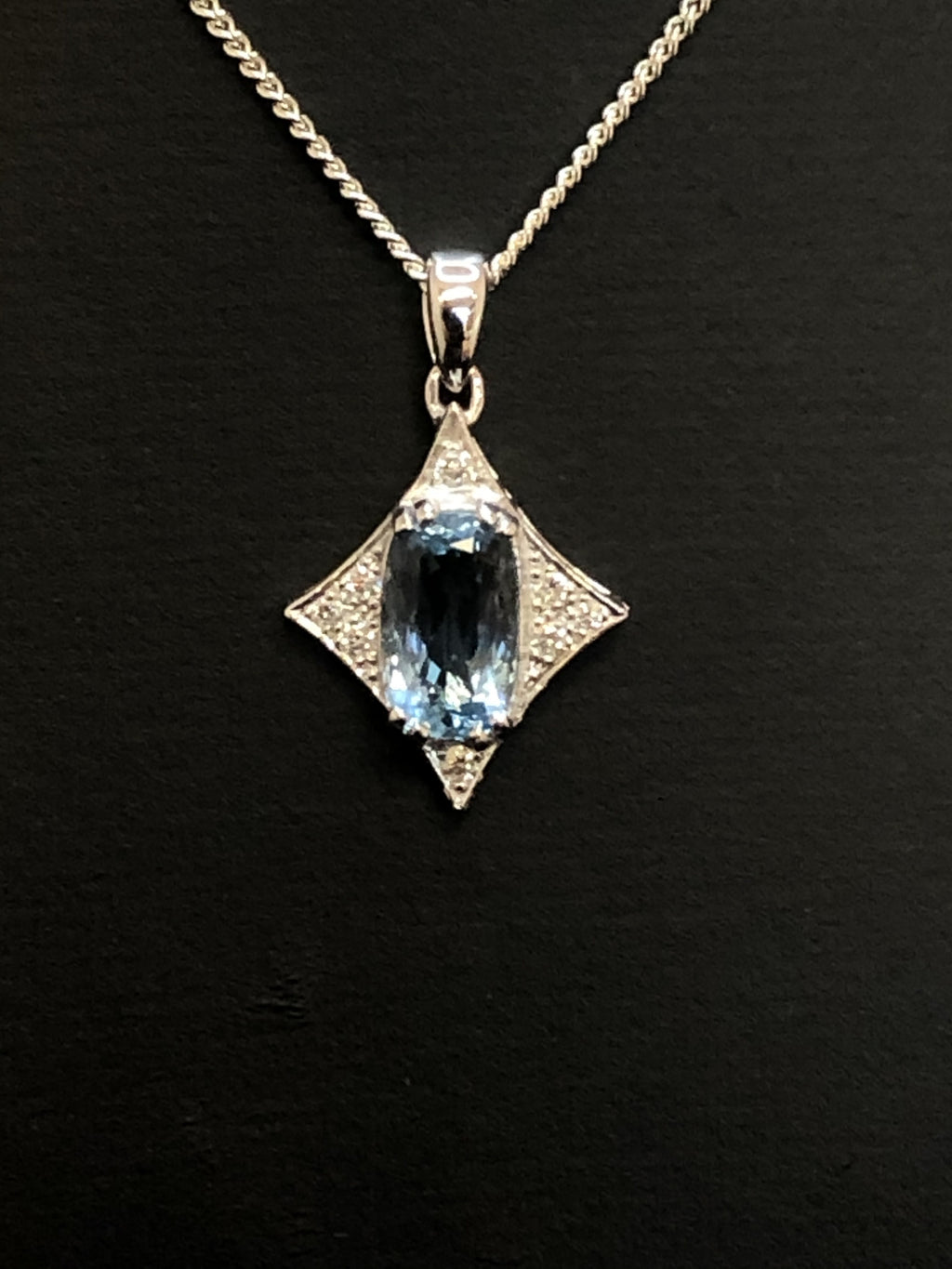 A close up front view of a large cushion cut aquamarine set in a clightly concave diamond shaped pendant, accented with small diamonds