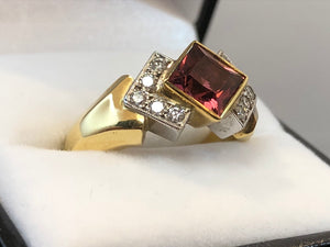 Side on close up of a princess cut red rubellite set in 18ct yellow gold, surrounded by 5 diamonds on each side set in 18ct white gold, on an 18ct yellow gold band