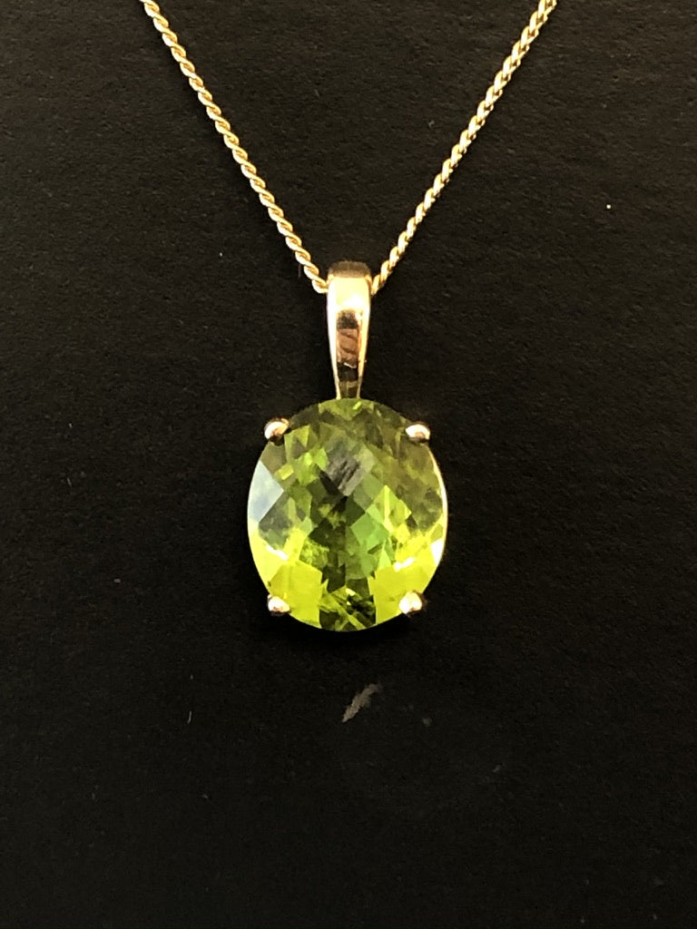 A close up view of a chequerboard cut peridot set in 10ct yellow gold