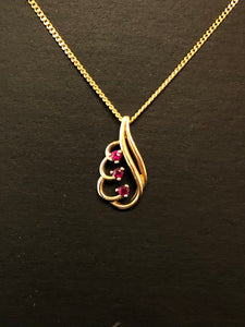 A close up view of a fancy open 10ct yellow gold and ruby pendant