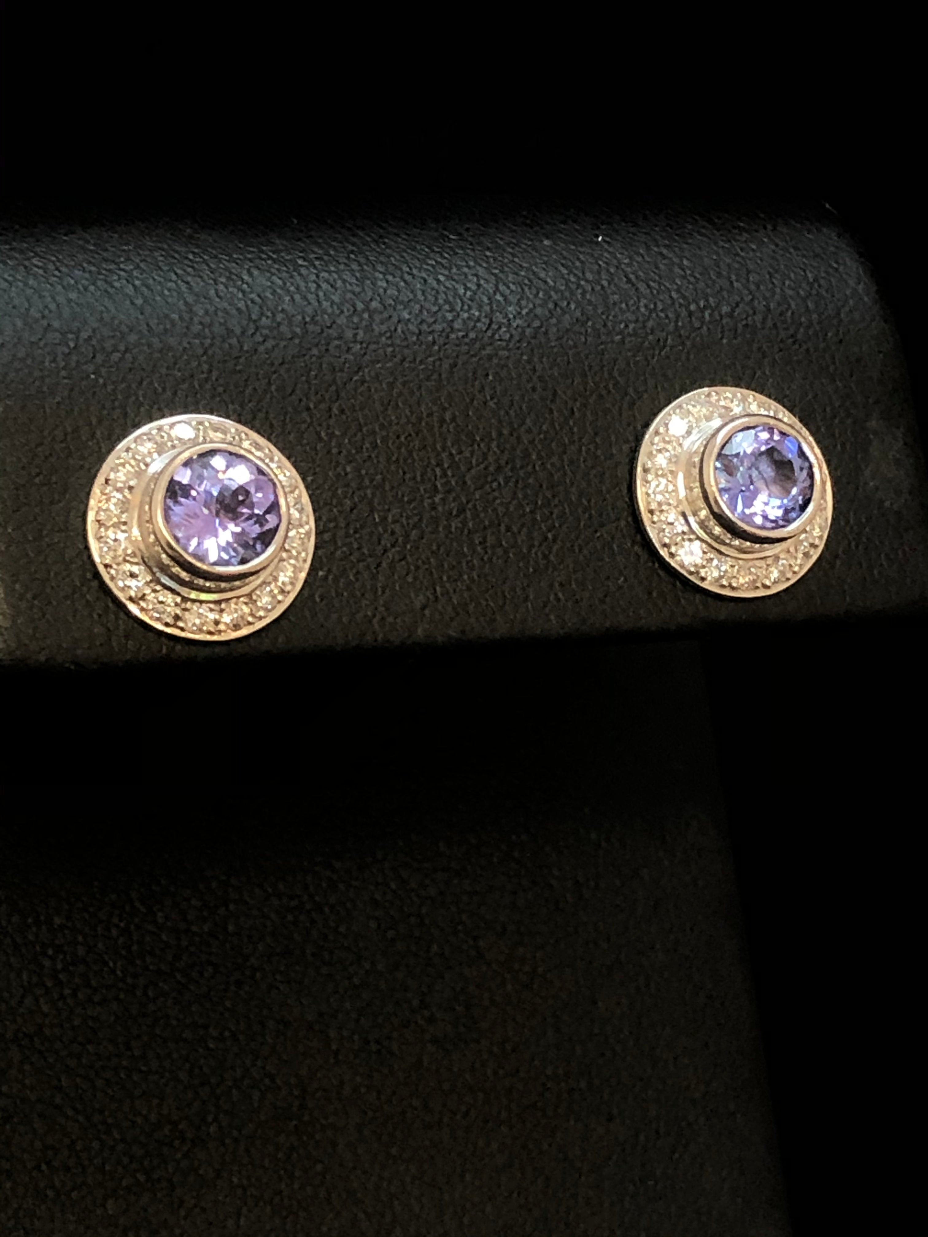 Side on close up of a pair of round earrings with a central violet-blue tanzanite in each, surrounded by small diamonds, set in 18ct white gold