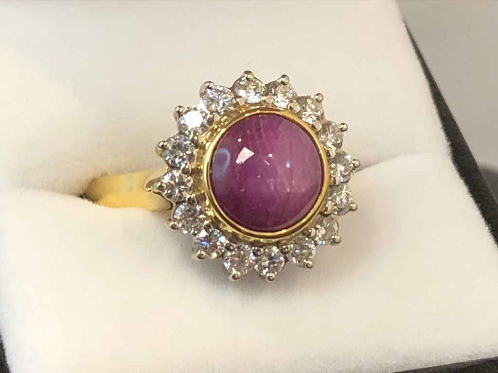 Close up side shot of a round cabochon star ruby set in 18ct yellow gold surrounded by 16 diamonds set in 18ct white gold, on an 18ct yellow gold band