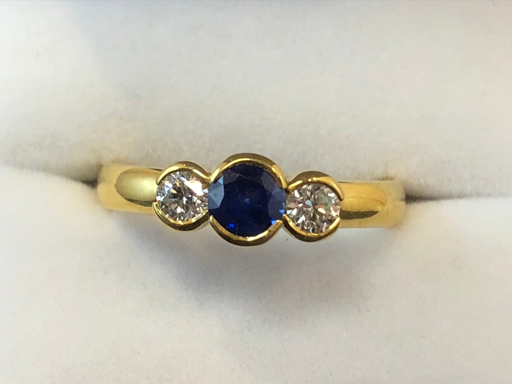 A close up of an 18ct yellow gold band with a deep blue central sapphire and two flanking diamonds in a rubover setting