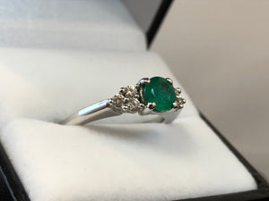 Close up side on view of a four-claw set deep green round cut emerald with a three-stone diamond trefoil on either side, set in 18ct white gold