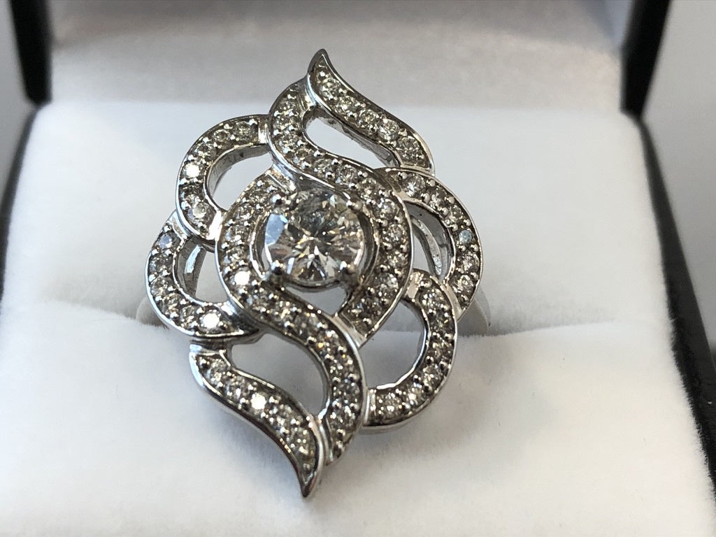 A front on close up of an 18ct white gold ring with 1ct of diamonds set in a fancy geometric rose shape