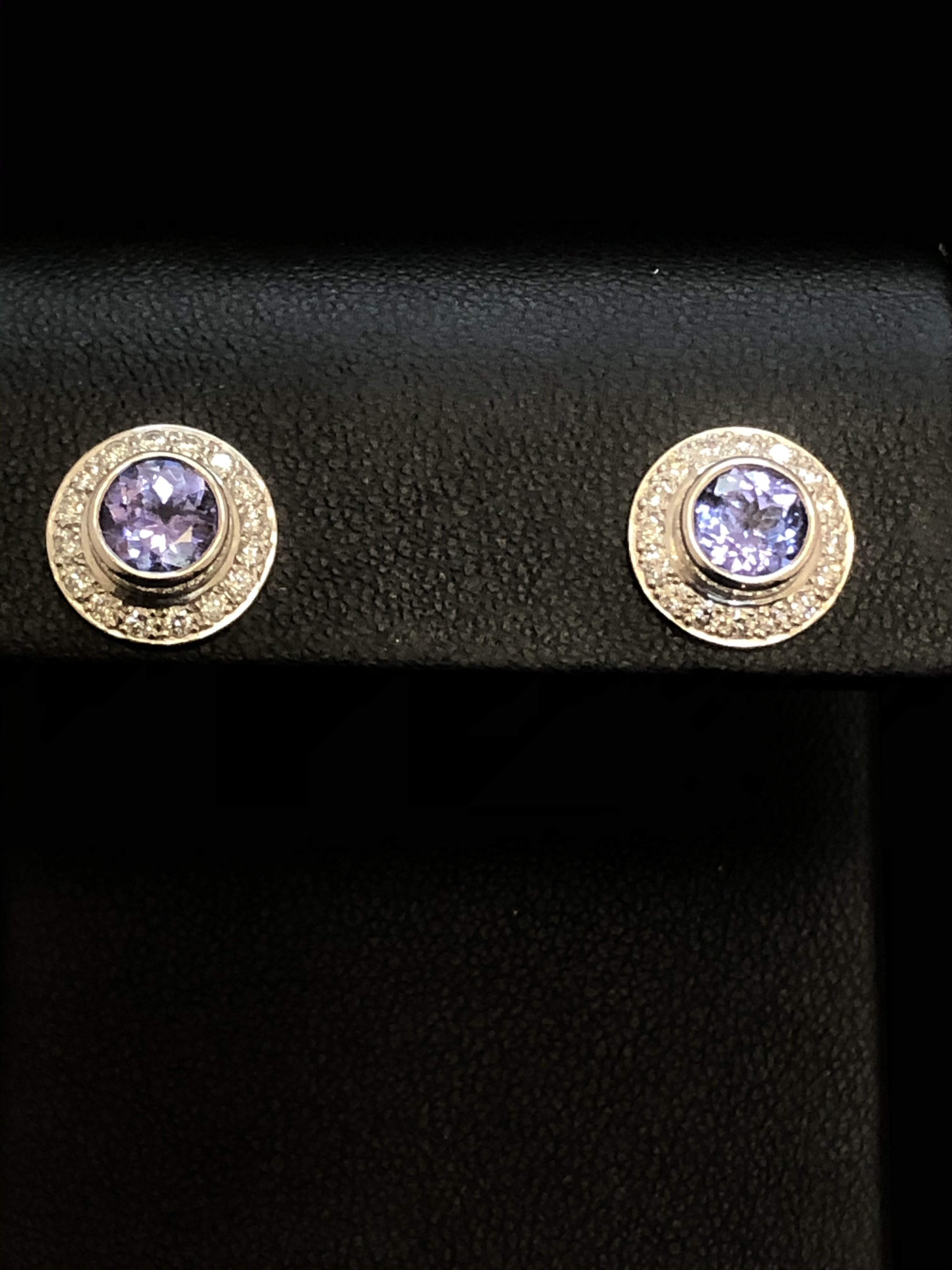 Close up of a pair of round earrings with a central violet-blue tanzanite in each, surrounded by small diamonds, set in 18ct white gold