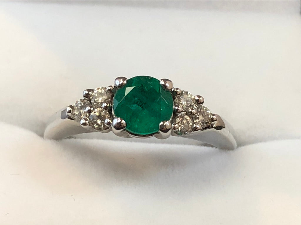 Very close up front on view of a four-claw set deep green round cut emerald with a three-stone diamond trefoil on either side, set in 18ct white gold