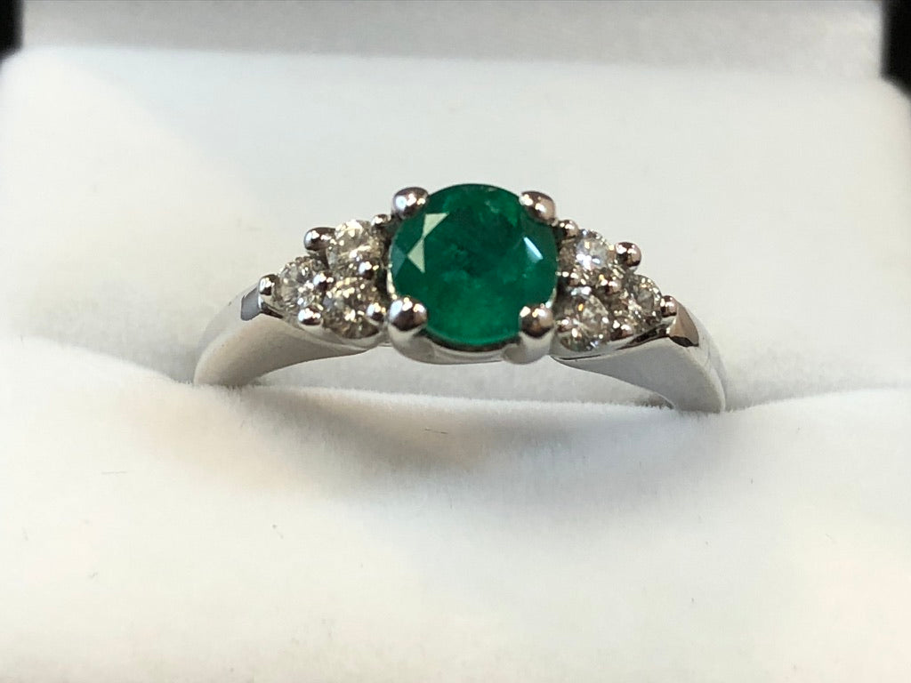 Close up front on view of a four-claw set deep green round cut emerald with a three-stone diamond trefoil on either side, set in 18ct white gold