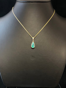 A long view of a solid black Australian opal, teardrop shaped, in a rubover setting, on a display chain