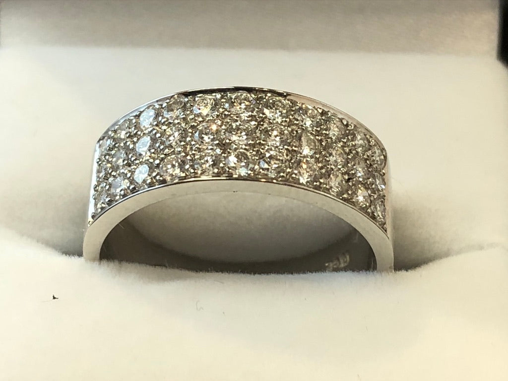 A front on close up of a wide 18ct white gold band with 3 rows of diamonds