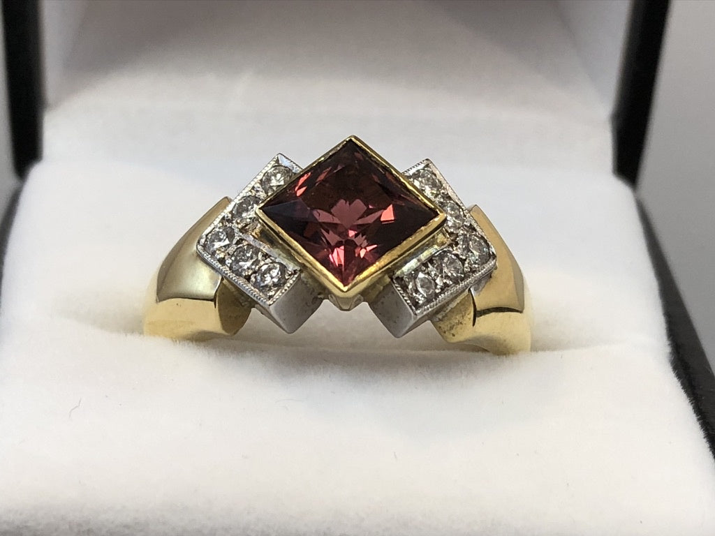Close up of a princess cut red rubellite set in 18ct yellow gold, surrounded by 5 diamonds on each side set in 18ct white gold, on an 18ct yellow gold band