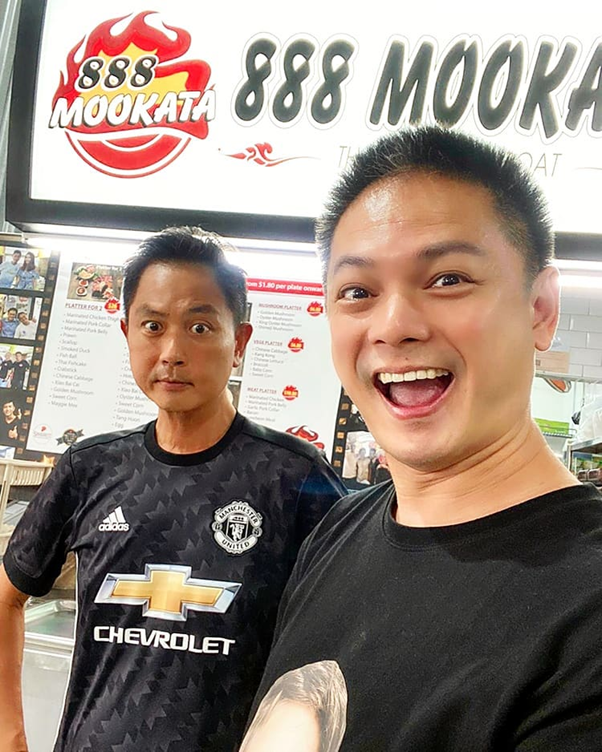 Mediacorp artistes Chor Chew Meng and Dennis Chew posing in front of their store, 888 Mookata