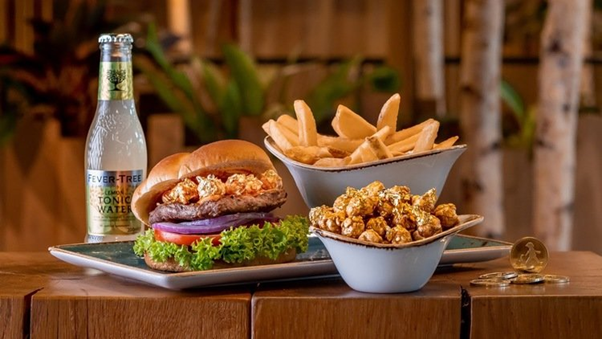 A beef burger topped with the signature Hans Im Glück sauce featuring The Kettle Gourmet's Kaya Butter Toast popcorn, garnished with edible gold flakes and accompanied with potato wedges and tonic water