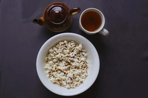 a pot of tea with a cup filled with it to pair with the popcorn