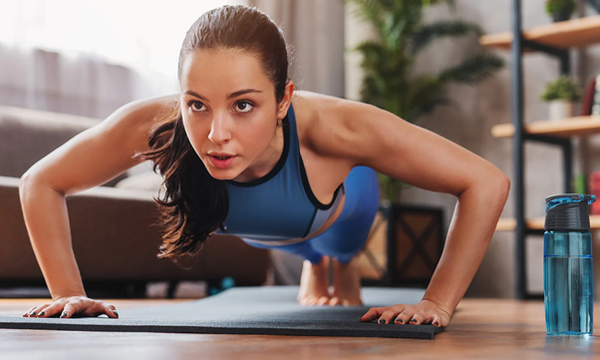 Determined young woman doing pushups: exercising at home
