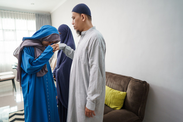 a Muslim young woman doing the salam(taking the elder's hand and putting it on her head) as a sign of respect to her elder