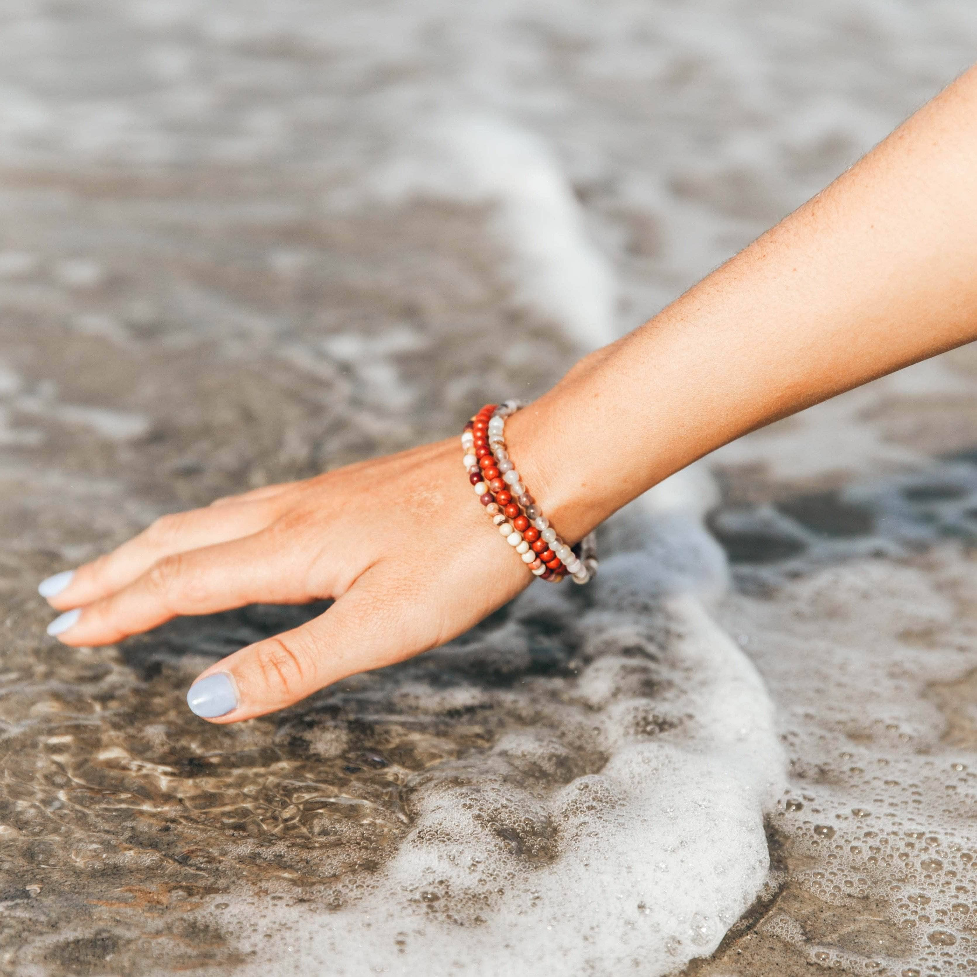courage and strength bracelets on arm of woman touching water