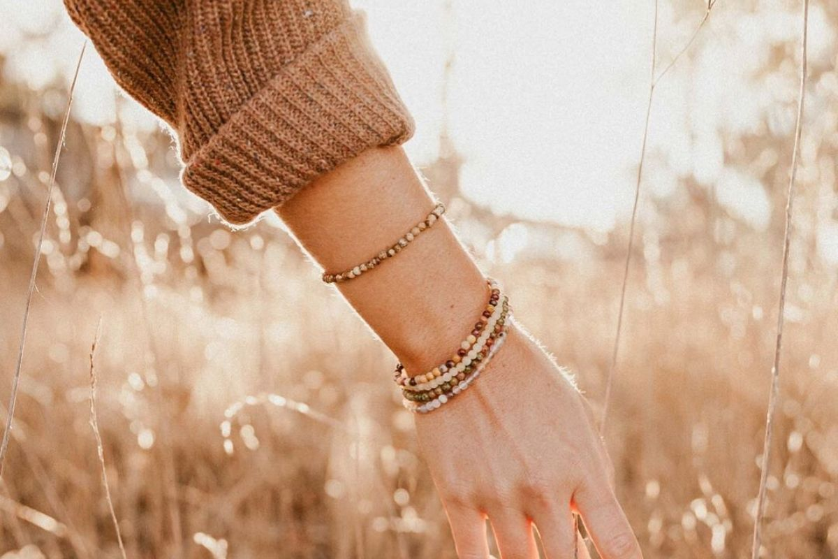 woman wearing tigers eye bracelet walking through wheat field