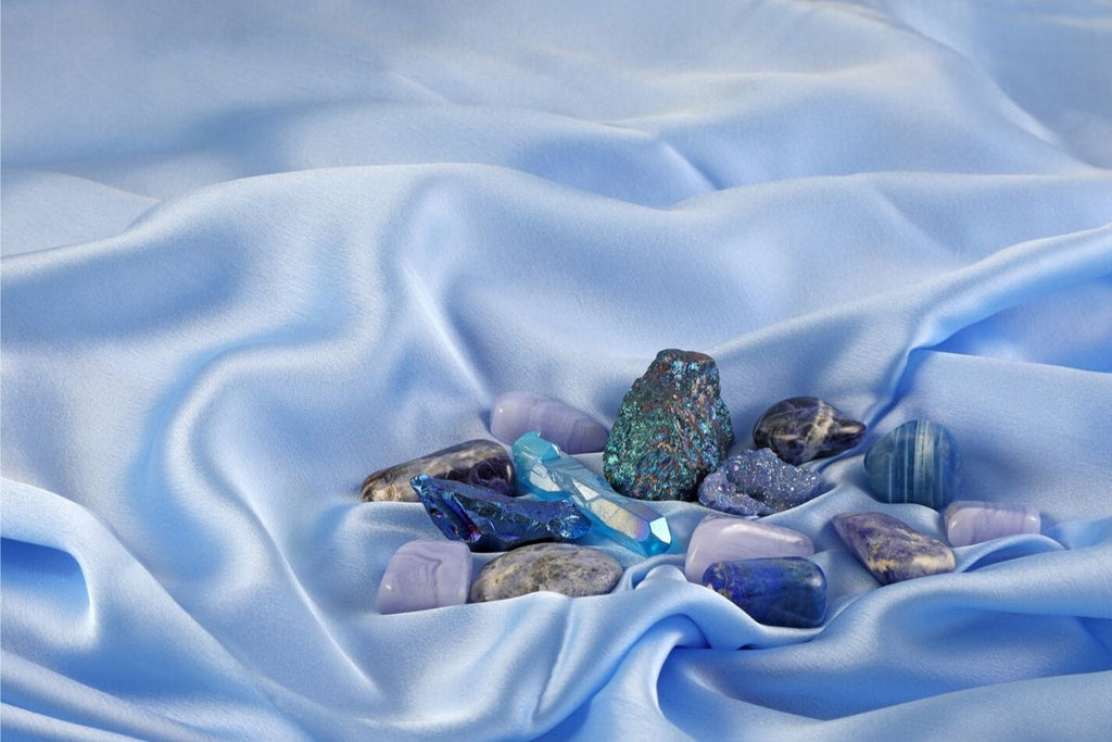 collection of stones including sodalite on blue silk