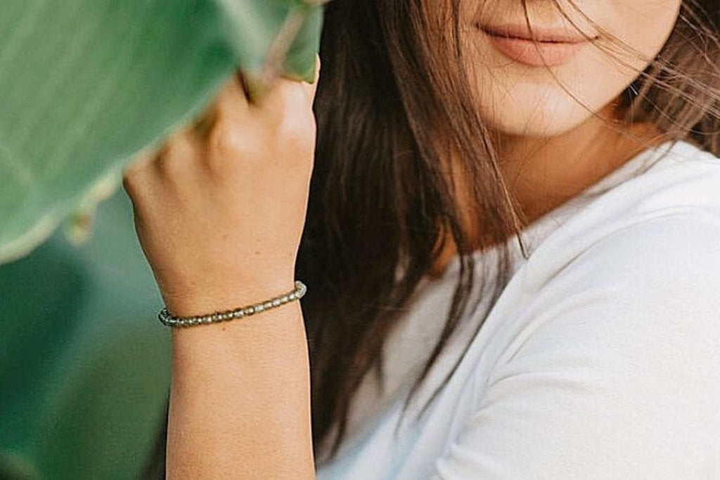 woman wearing peridot gemstone bracelet