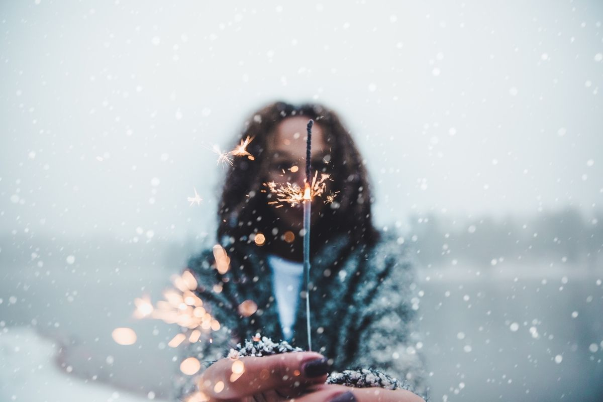 woman with sparkler in snow