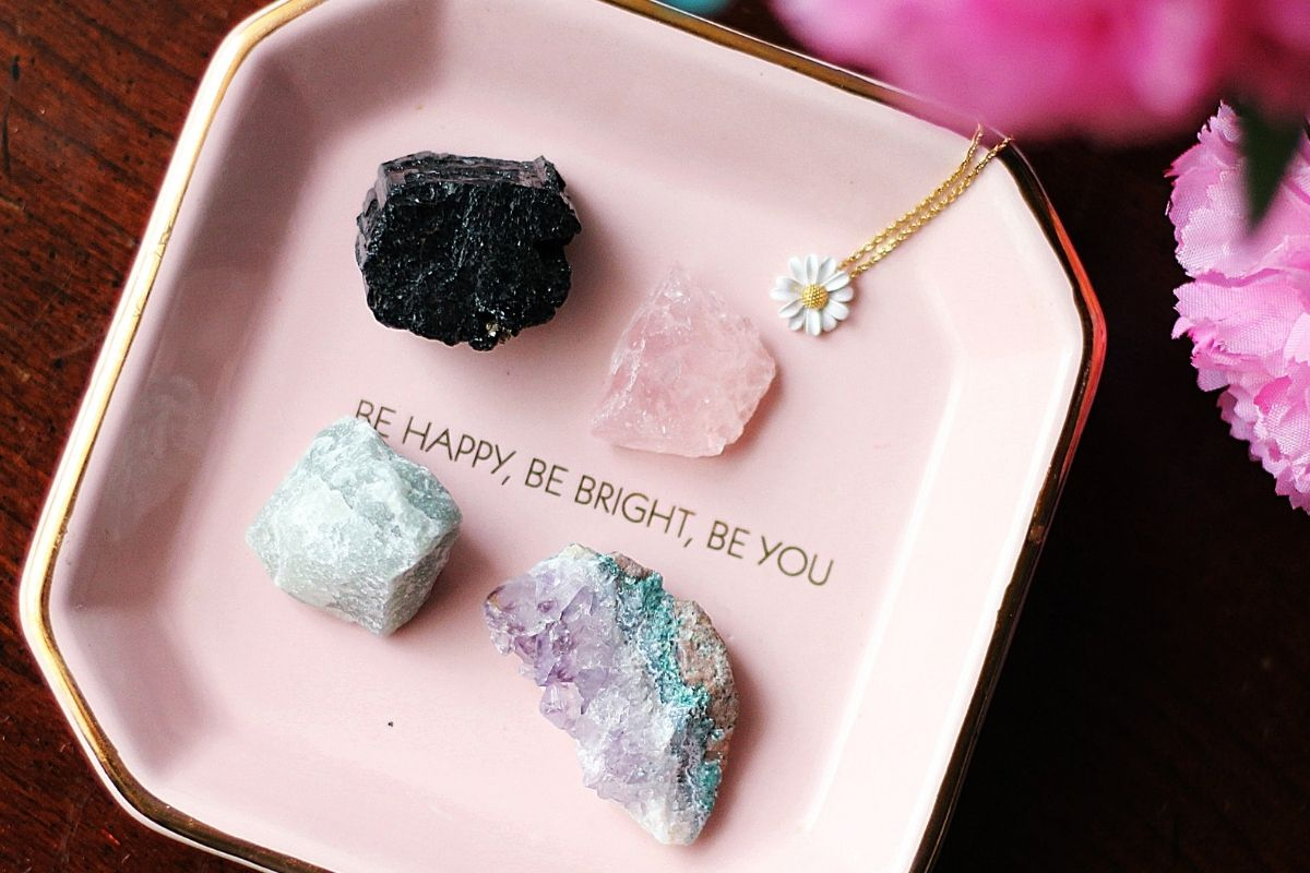 four gemstones in a pink dish