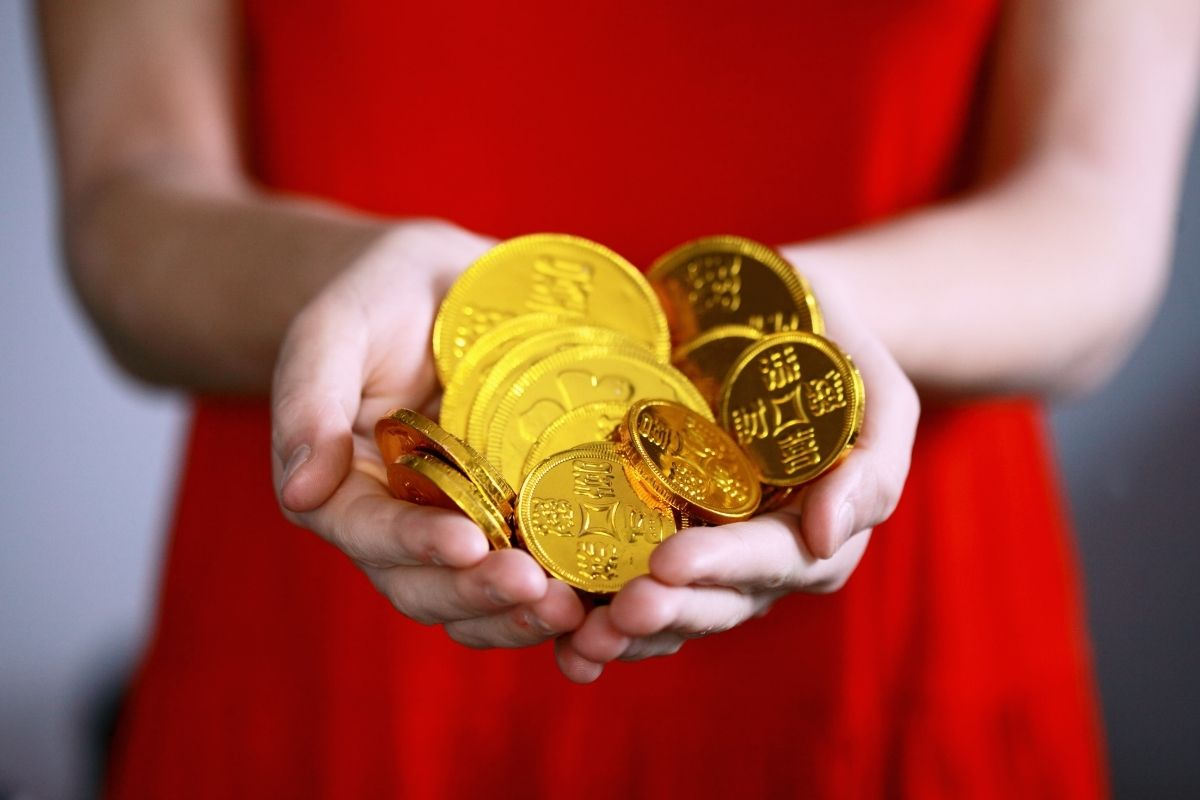 woman in red dress holding gold coins