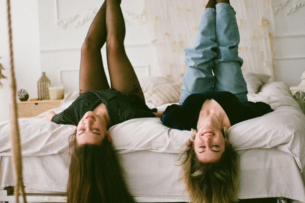 two girls lying upside down on a bed