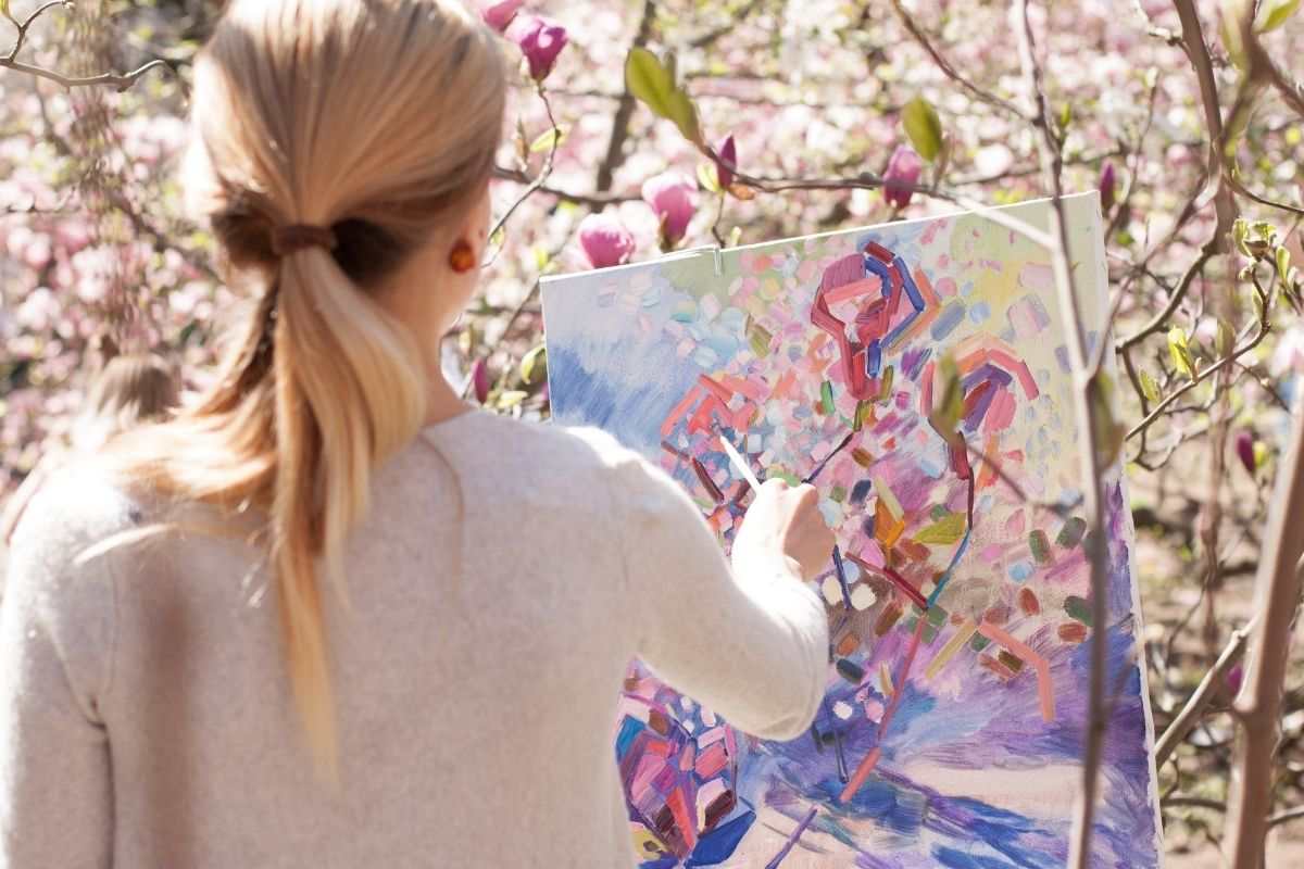 woman painting in forest