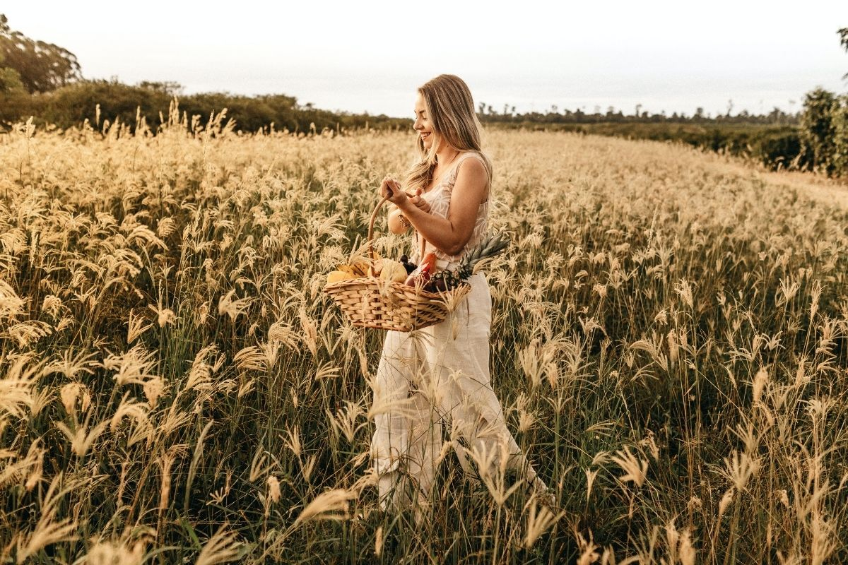 woman with basket walking in wheat field