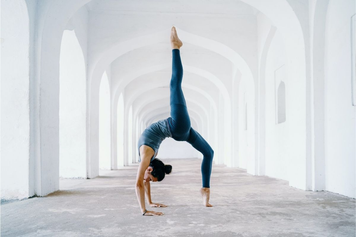 woman in blue doing yoga against white arches