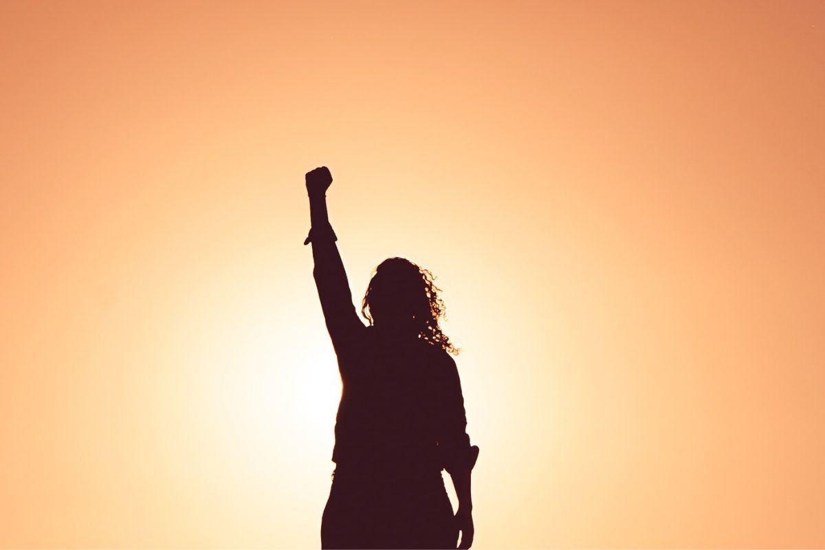 shadow of woman raising fist against sunset
