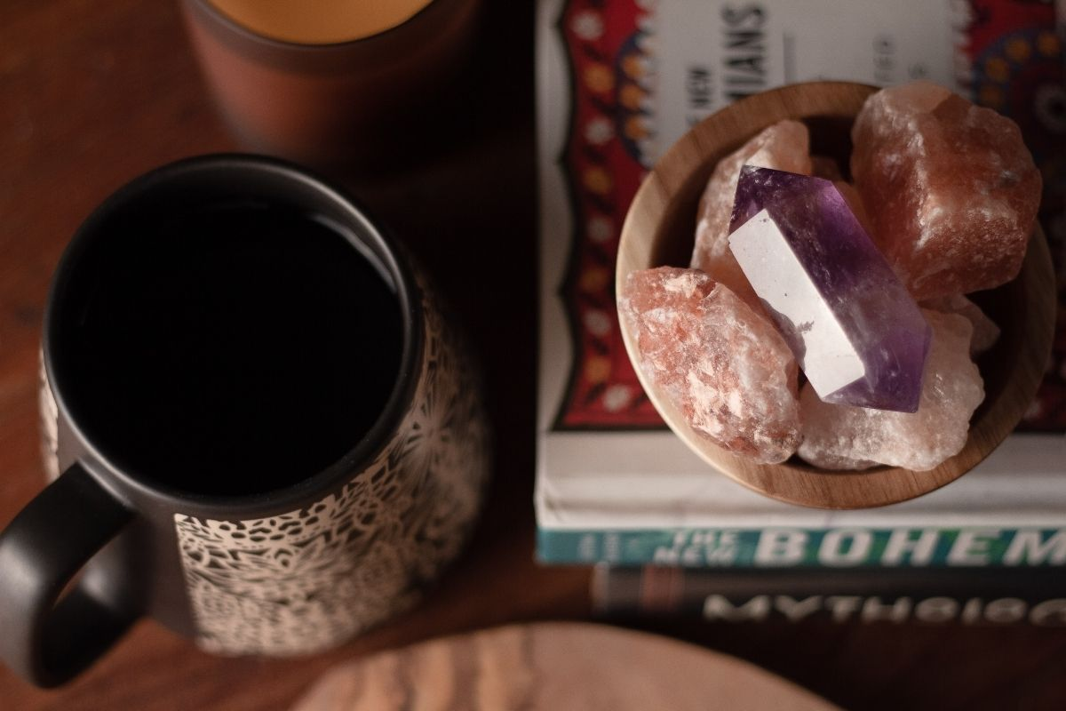 bowl of crystals next to coffee cup